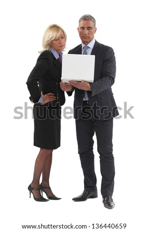 Senior business couple stood with laptop - stock photo