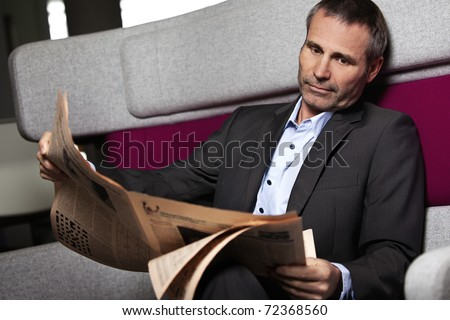 Senior business executive having a break in office and reading newspaper. - stock photo