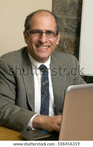 senior business executive in conference room office giving presentation with computer laptop - stock photo