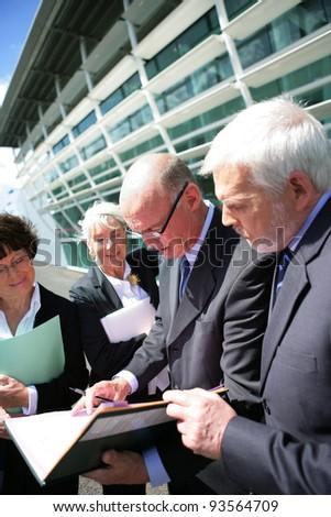 Senior business group meeting outdoors - stock photo