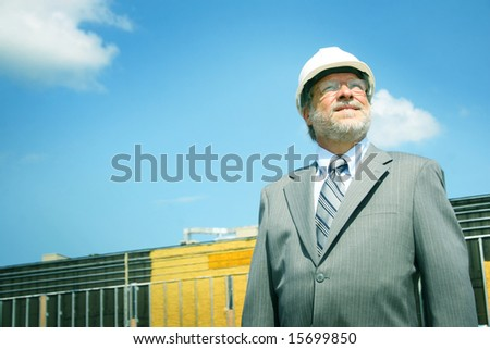 Senior business man and white hard hat - stock photo