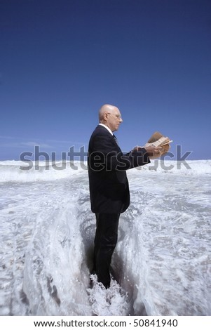 Senior business man reading newspaper standing in ocean wave, side view - stock photo