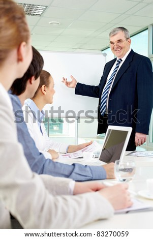 Senior business man showing something on a whiteboard to his colleagues - stock photo