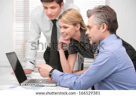 Senior  business man showing something on laptop. Sitting together with group of business people in modern office  - stock photo
