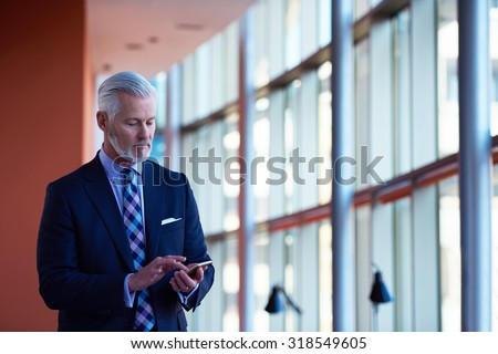 senior business man talk on mobile phone  at modern bright office interior - stock photo