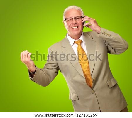 Senior Business Man Talking On Phone Isolated On Green Background - stock photo