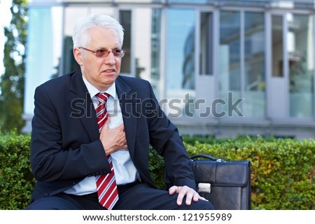 Senior business man with aching heart holding his chest - stock photo
