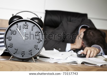 Senior business person being shocked after receiving bad news on cell phone, sitting at office desk behind alarm clock showing five minutes to twelve. - stock photo