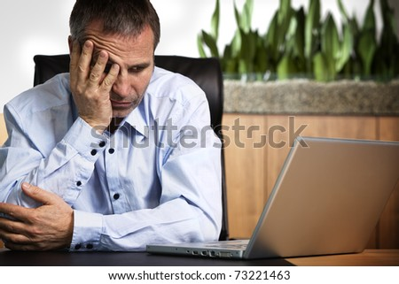 Senior business person in blue shirt sitting at office desk looking at laptop and being frustrated about computer or software crash.