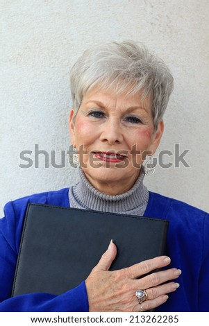 Senior Business Woman Happy and Confident Mature Elderly Senior Citizen Holding a Folder With Her Hands - stock photo