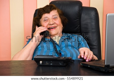 Senior business woman having a funny conversation by telephone and she laughing - stock photo