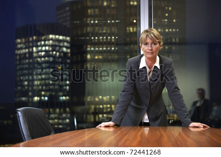 Senior Business woman leaning on table in boardroom looking at camera - stock photo