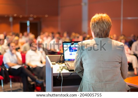Senior business woman lecturing at Conference. Audience at the lecture hall. - stock photo