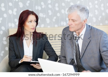Senior businessman and mid age businesswoman discuss about a business