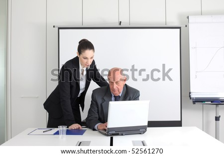Senior businessman and younger businesswoman working on a laptop - stock photo