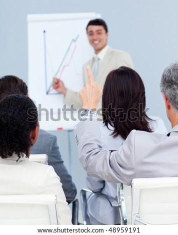 Senior businessman asking a question at a presentation with his colleagues - stock photo