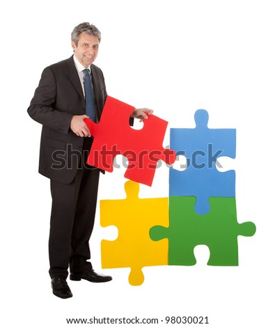Senior businessman assembling a jigsaw puzzle. Isolated in white - stock photo