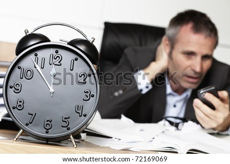 Senior businessman being shocked after receiving bad news on cell phone, sitting at office desk behind alarm clock showing five minutes to twelve. - stock photo