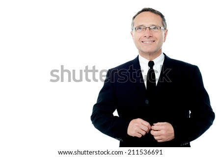 Senior businessman button his suit jacket, looking up - stock photo