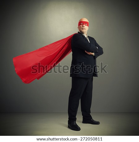 senior businessman dressed as a superhero in red mask and cloak over dark grey background - stock photo