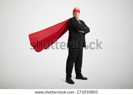 senior businessman dressed as a superhero in red mask and cloak over light grey background - stock photo