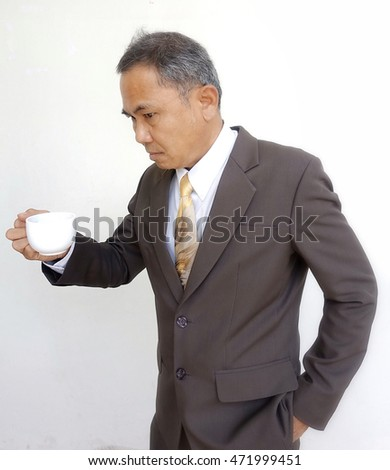 Senior businessman feeling sick after long meeting holding a cup of tea