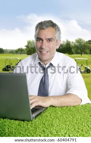 senior businessman golf course working computer green grass desk [Photo Illustration] - stock photo