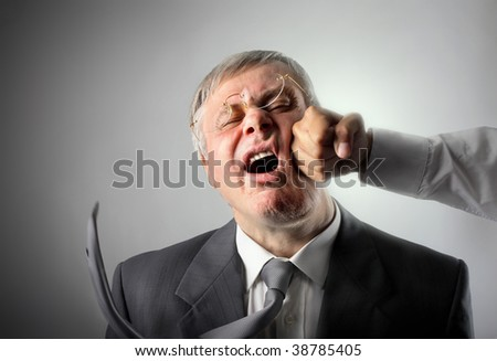 senior businessman hit on the face by punch - stock photo