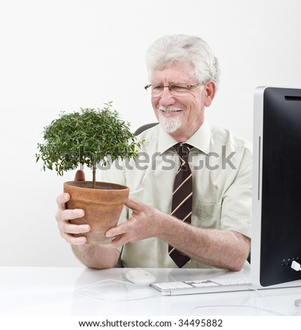 senior businessman holding a potted plant over white - stock photo
