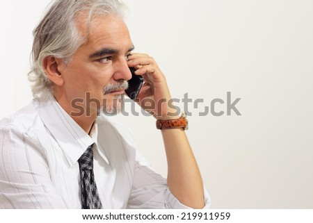Senior businessman holding mobile phone, isolated on white background, with copy space - stock photo