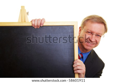 Senior businessman in a suit behind a chalkboard - stock photo