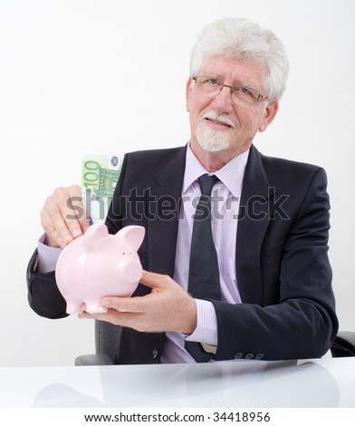 senior businessman inserting one hundred  euro bill in  a piggy bank
