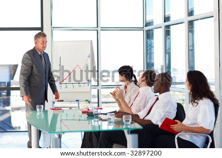 Senior businessman interacting with his team in a presentation - stock photo