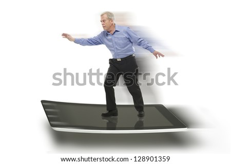 Senior businessman keeping balance on a PC tablet, with blurred motion effect - stock photo