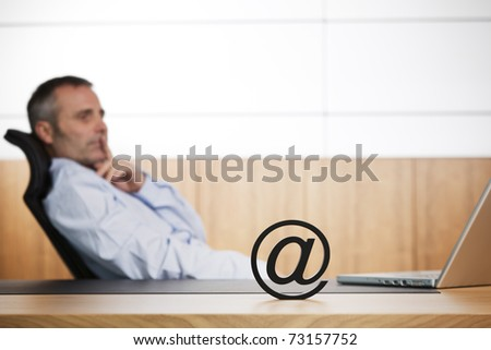 Senior businessman leaning back in office chair thinking and looking at laptop, with at symbol in foreground symbolizing e-business opportunities. - stock photo