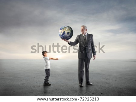 Senior businessman lending the earth to a child - stock photo