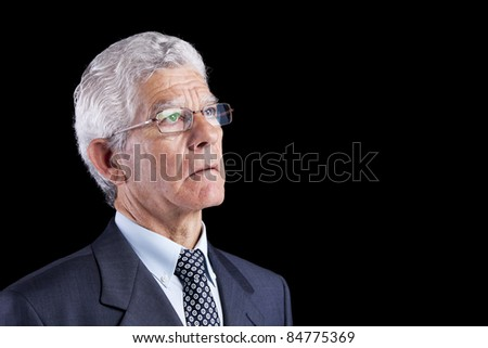 Senior businessman looking up to the copyspace (isolated on black) - stock photo