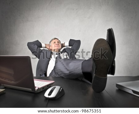 Senior businessman lying on his office chair with his feet on the desk - stock photo