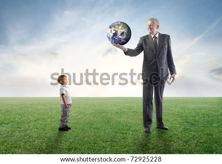 Senior businessman on a green meadow lending the Earth to a child - stock photo