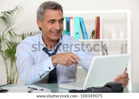 Senior businessman pointing at laptop - stock photo