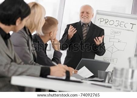 Senior businessman presenting on meeting to mid-adult coworkers, smiling, gesturing with both hands.? - stock photo