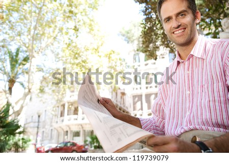Senior businessman reading a newspaper while sitting down in a classic city square, outdoors. - stock photo