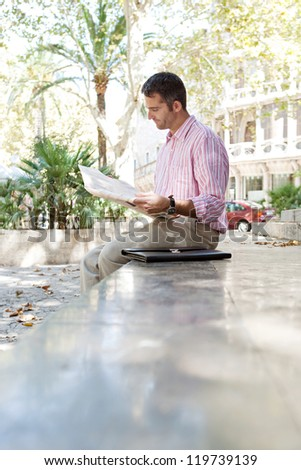 Senior businessman reading a newspaper while sitting down on a stone step in a classic city square, outdoors. - stock photo