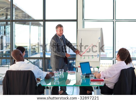 Senior businessman reporting to graphs in a presentation with his colleagues - stock photo