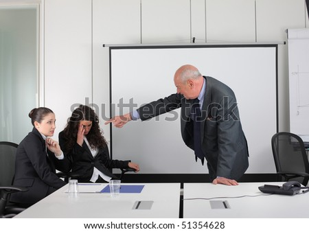 Senior businessman reproaching two businesswomen - stock photo