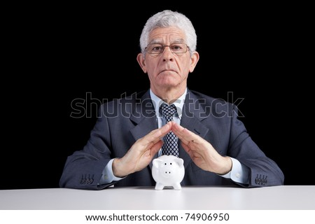 Senior businessman saving some money for his retirement (isolated on black) - stock photo
