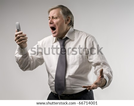 Senior businessman screaming against a mobile phone - stock photo