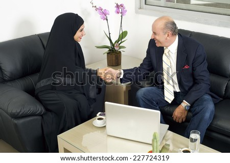 Senior Businessman Shaking hands with Woman wearing hijab, Multiracial Businesspeople shaking hands in office  - stock photo