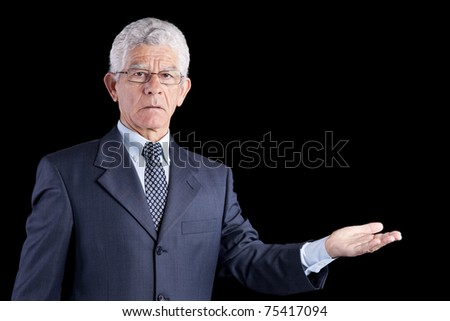 senior businessman showing something with his hands (isolated on black - stock photo