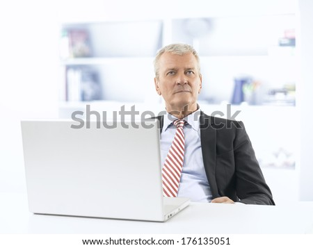Senior businessman sitting at desk and working on laptop in office.